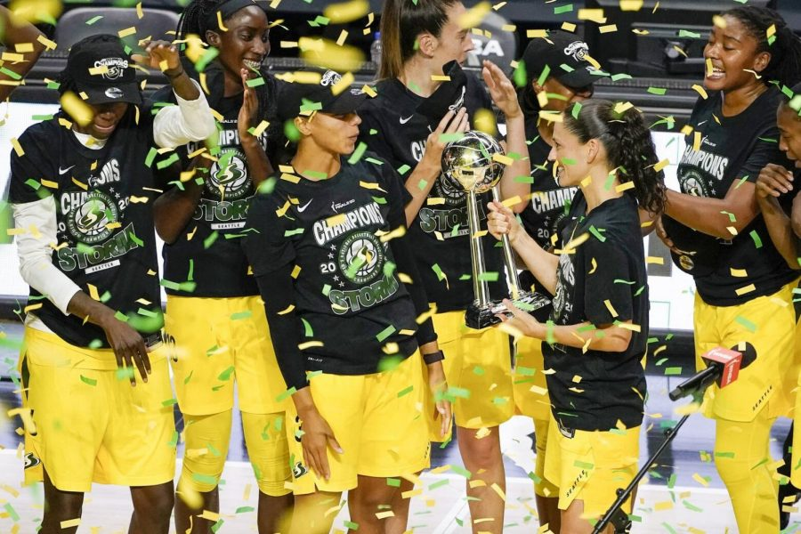 Seattle Storm's Sue Bird carries the WNBA Championship trophy over to her teammates after sweeping the Las Vegas Aces in three games.  Photo By: Chris O'Meara / Associated Press.