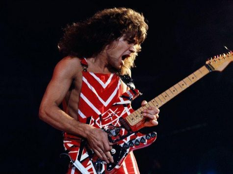 Van Halen performing with his signature striped guitar, originally designed with electrical tape. 									        Photo by Fabio Nosotti.